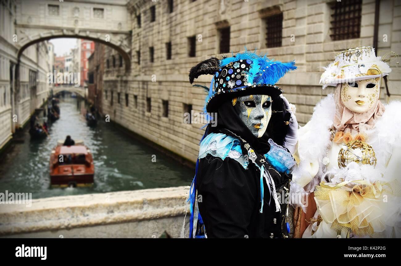 Due persone che indossano i costumi per il Carnevale di Venezia, vicino al Ponte di Vista (Ponte dei Sospiri) vestita in opposta a colori in bianco e nero Immagini Stock