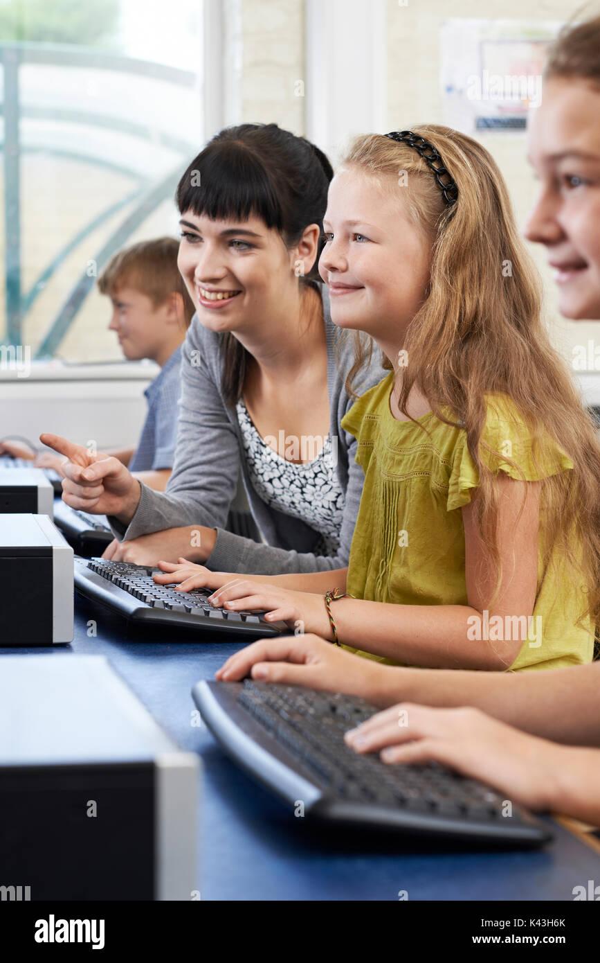 Femmina pupilla elementare in Classe Computer con insegnante Immagini Stock