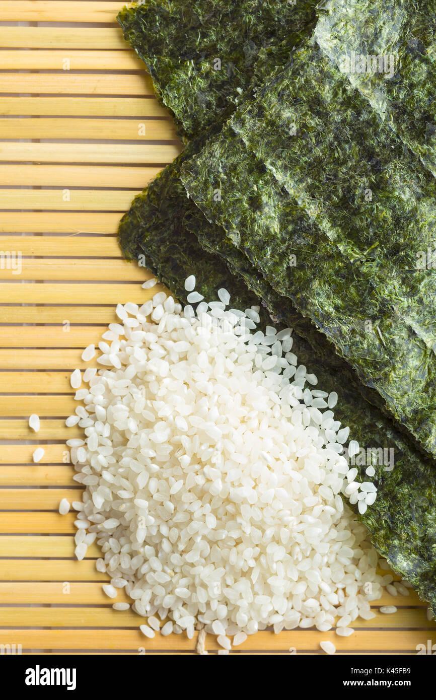 Verde foglio di Nori e riso sushi sul tappetino di bambù. Vista dall'alto. Immagini Stock
