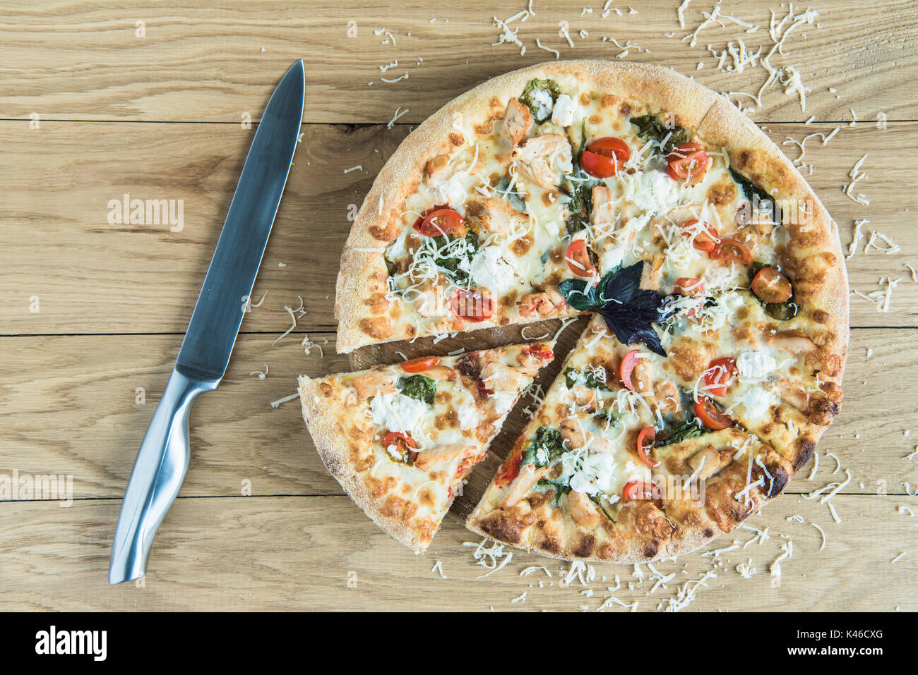 Vista superiore della pizza italiana con il coltello sul tavolo in legno Immagini Stock