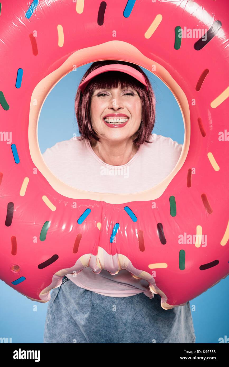 Sorridente donna anziana tenuta anello galleggiante a forma di ciambella Immagini Stock