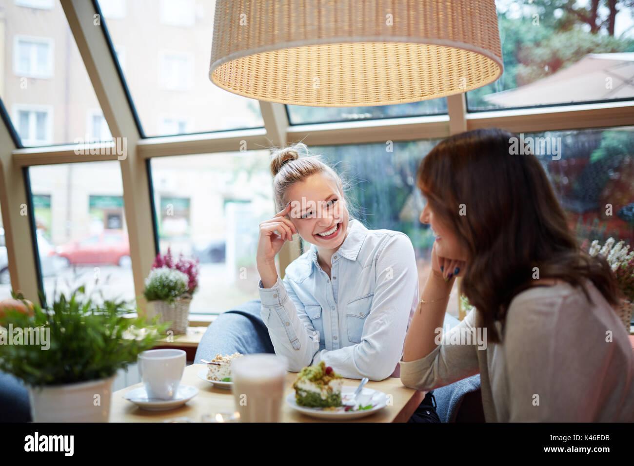 Ritratto di giovane donna avente bella conversazione presso il cafe. Immagini Stock
