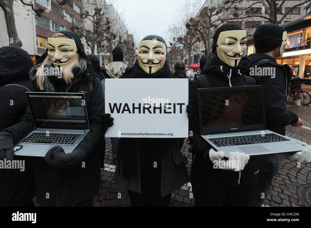 Attivisti anonimi indossando maschere Guy Fawkes tenendo UNA verità segno Foto Stock