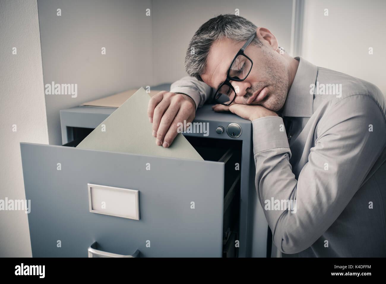 Armadio Archivio Ufficio : Stanco pigro lavoratore di ufficio appoggiato su di un armadio