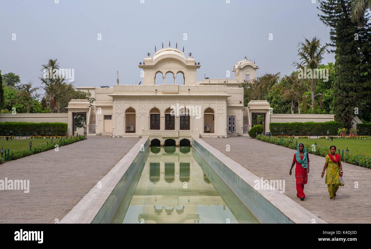 Giardini Pinjore (Yadavindra Gardens) costruito per le concubine del righello.Il palazzo si riflette nell'acqua. Donne indù a piedi sulle terrazze. Immagini Stock