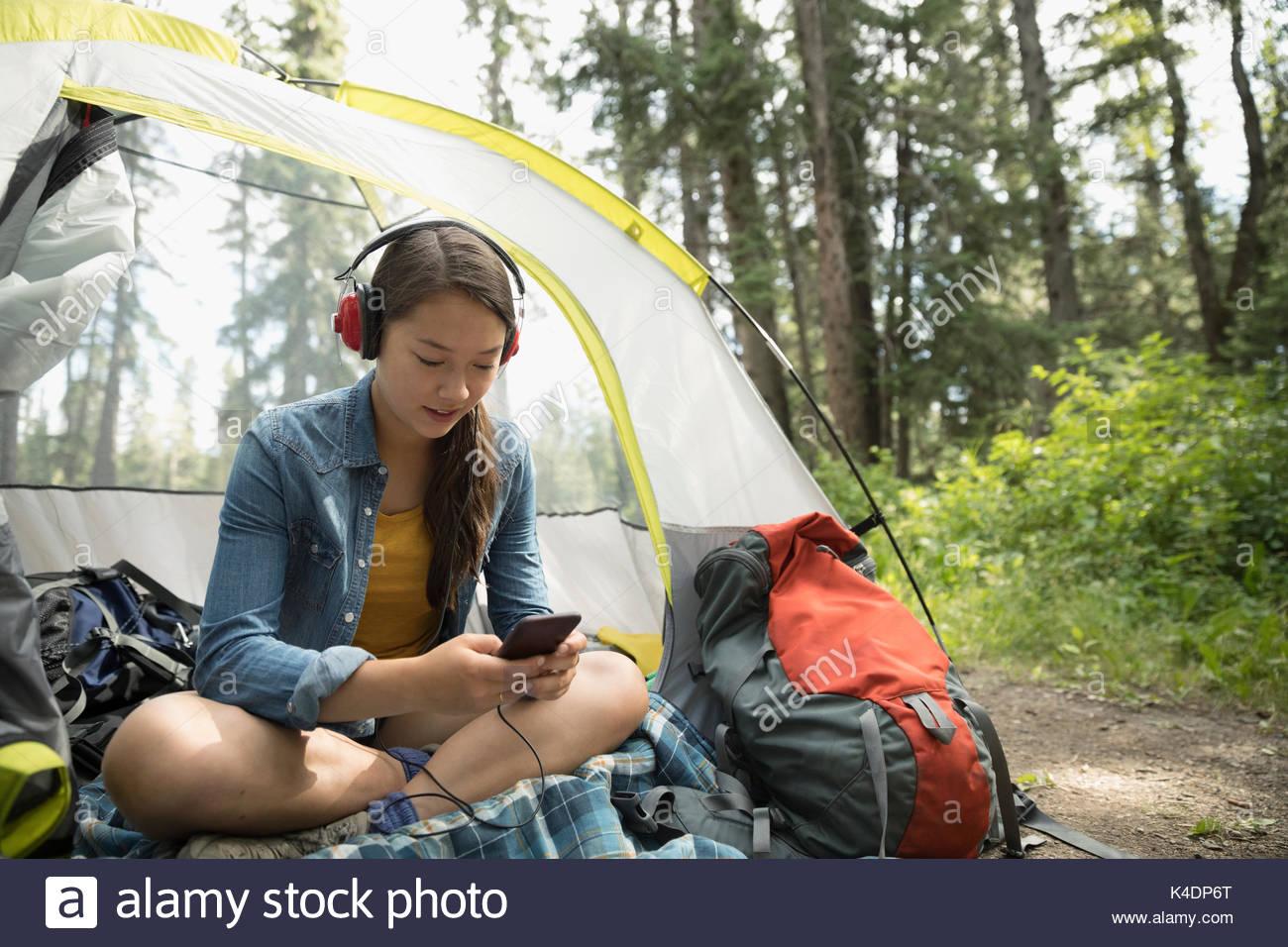 Ragazza adolescente rilassante, camping e ascolto di musica con le cuffie e il lettore mp3 in tenda Immagini Stock