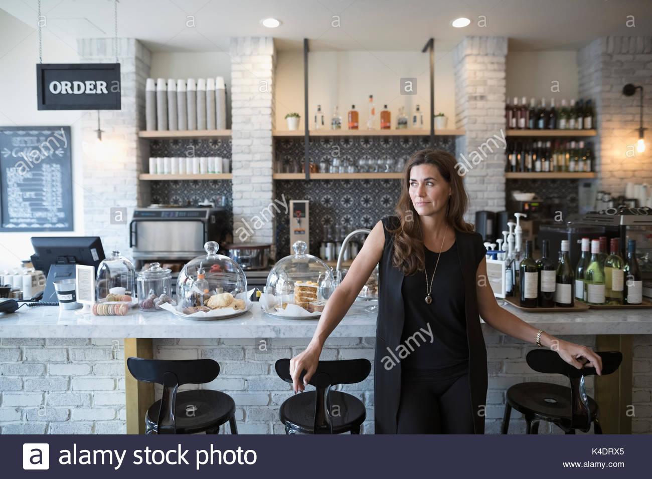Malinconici femmina proprietario cafe guardando lontano Immagini Stock