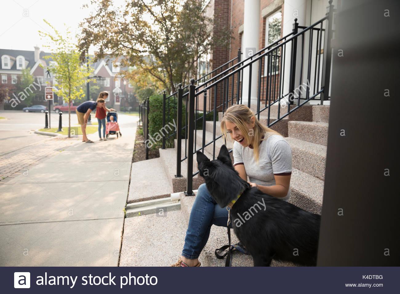Donna sorridente con il cane sui passi nelle vicinanze Immagini Stock
