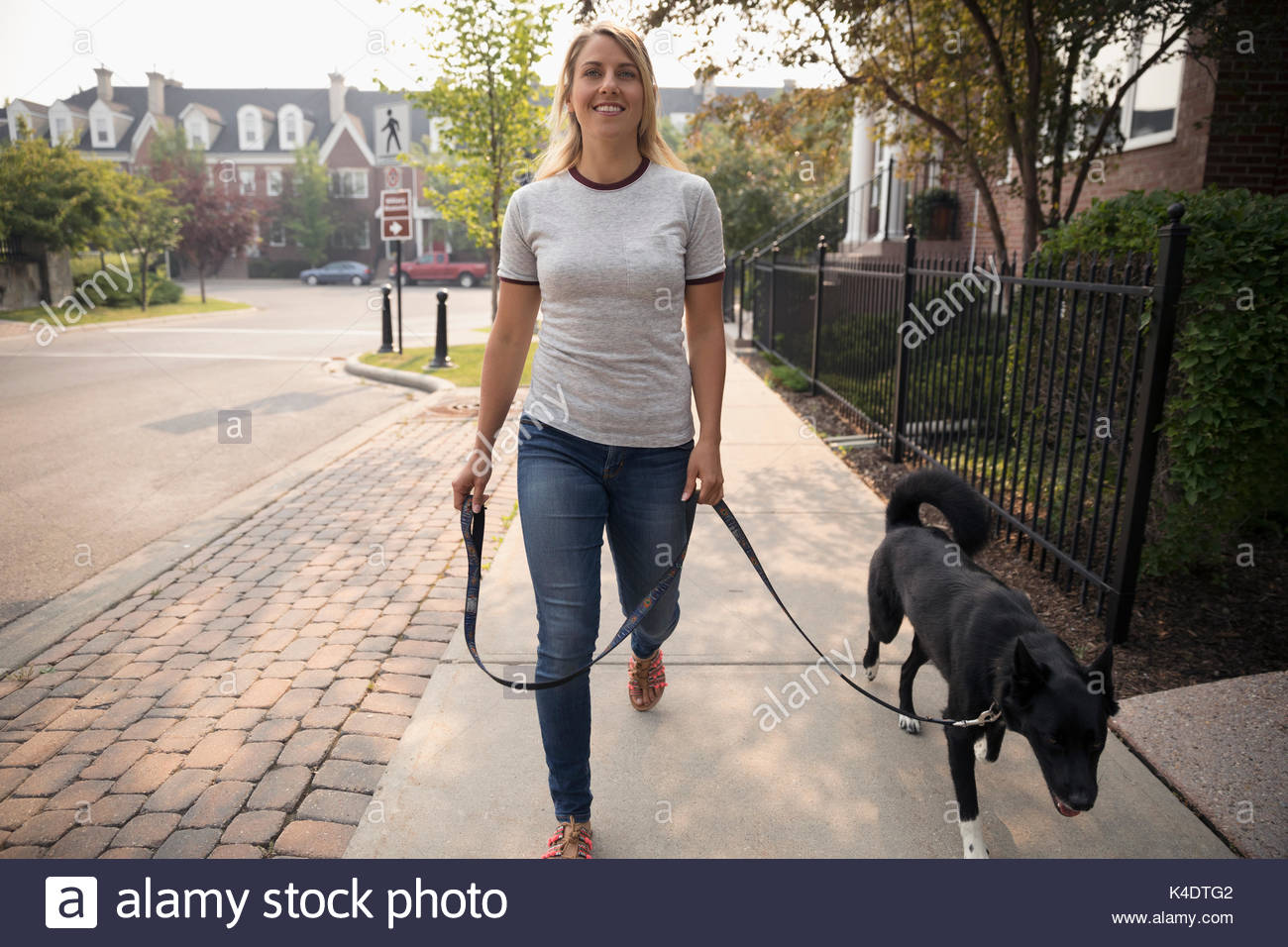 Donna sorridente walking cane al guinzaglio sul marciapiede di vicinato Immagini Stock