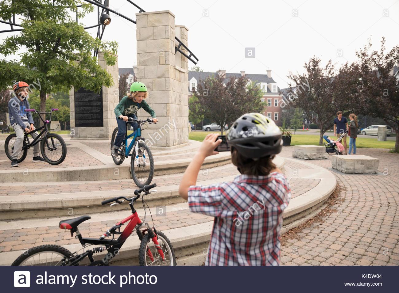 Ragazzo con smart phone di filmare gli amici di andare in bicicletta sulle fasi di stazionamento Immagini Stock