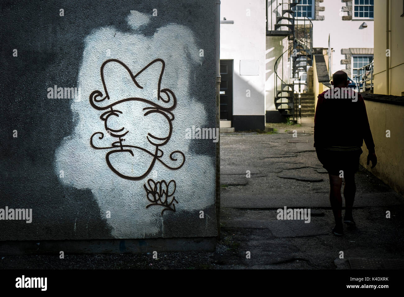 Graffiti - una figura a piedi passato graffiti spruzzato su una parete in truro city centre in Cornovaglia. Immagini Stock