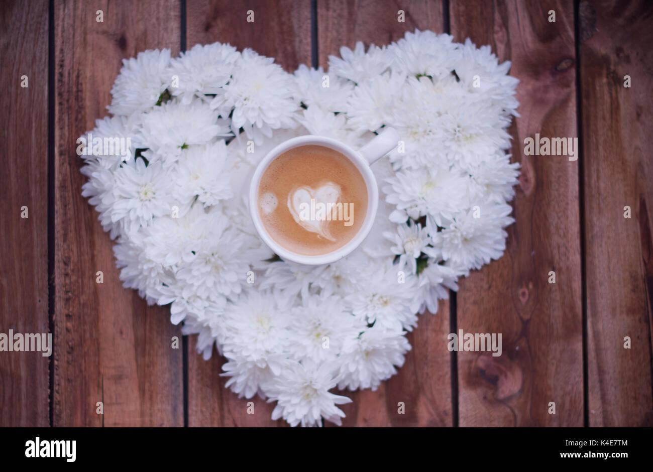 Cuore di fiori bianchi. mattina e caffè espresso. Il Romance. Sfondo di legno. Regalo romantico Immagini Stock