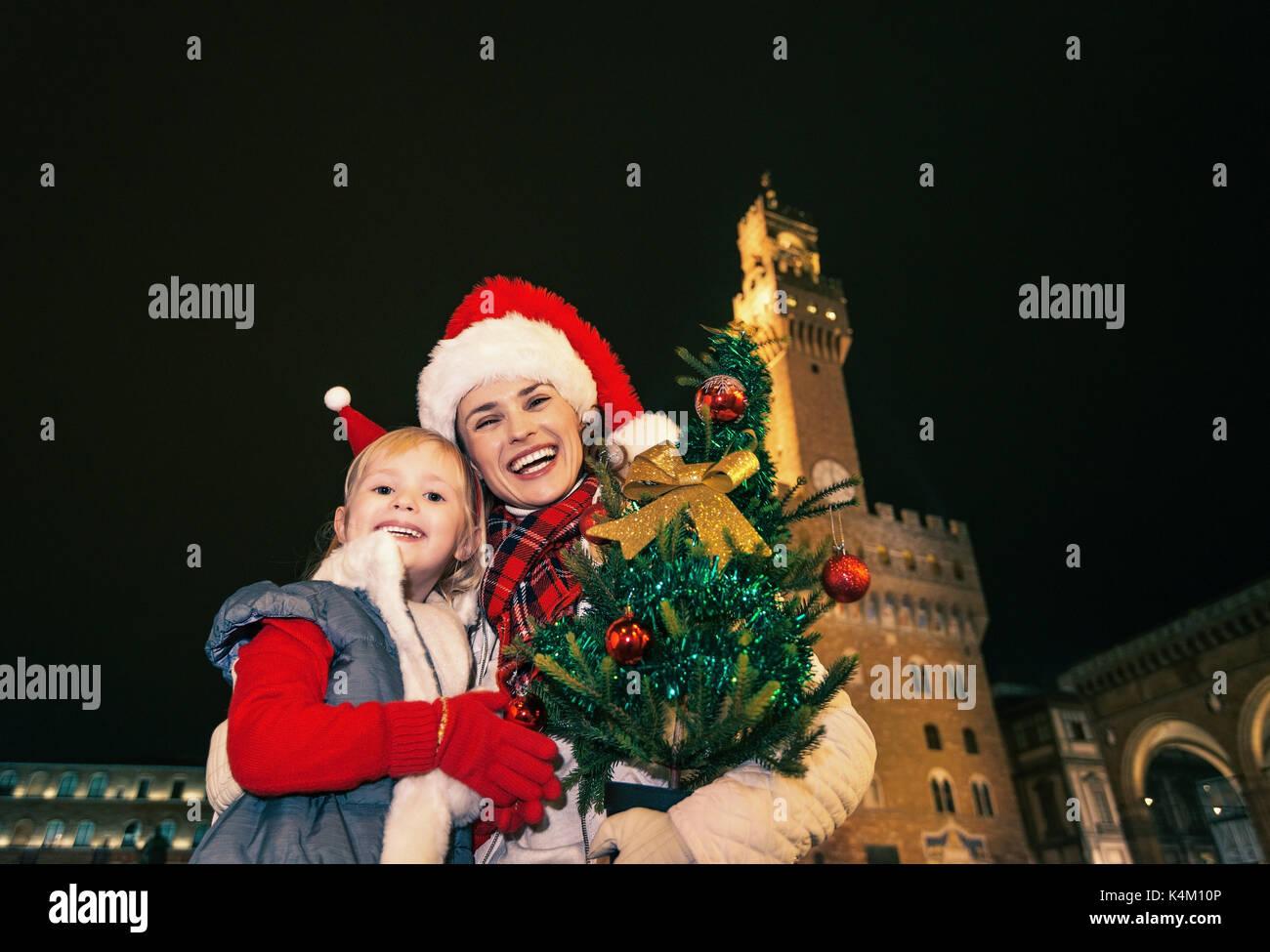 Viaggio pieno di ispirazione al tempo di Natale a Firenze. ritratto della  moderna sorridente madre 940029418d07