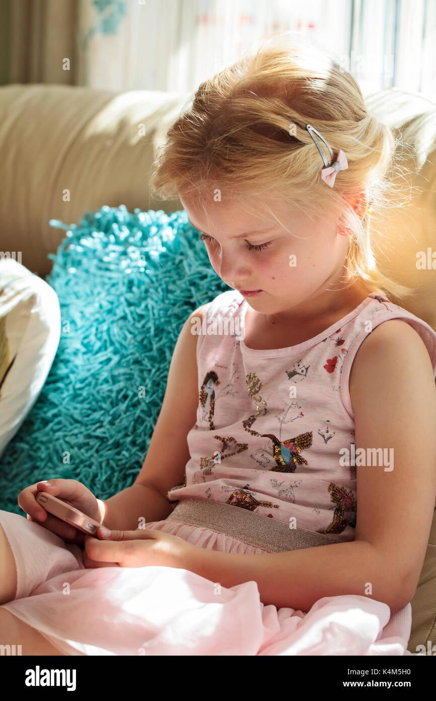Bambina gioca con smart phone Immagini Stock