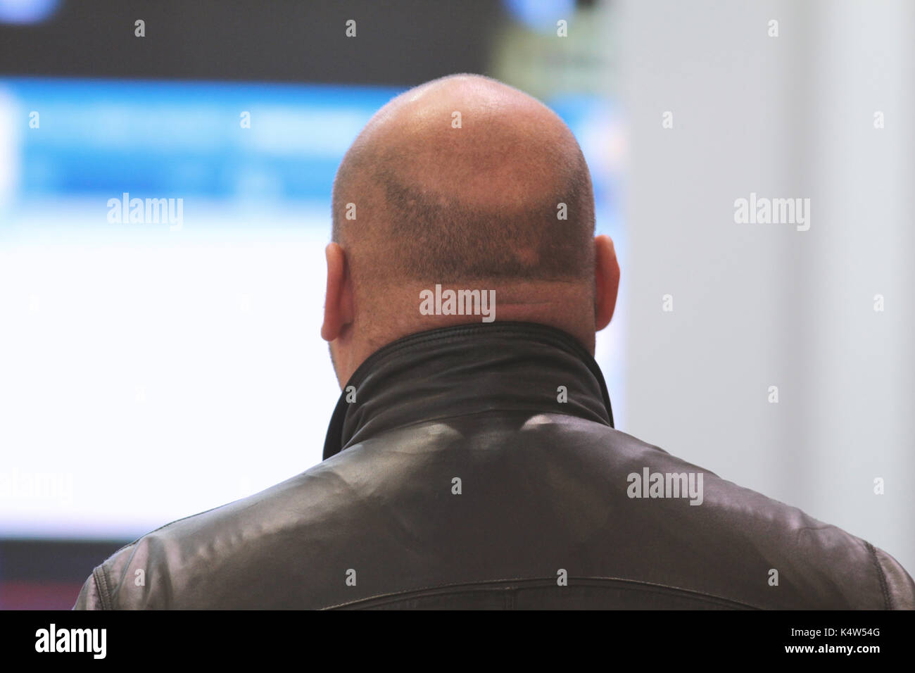Grande uomo calvo in giacca di pelle in sala conferenza - Vista posteriore Immagini Stock