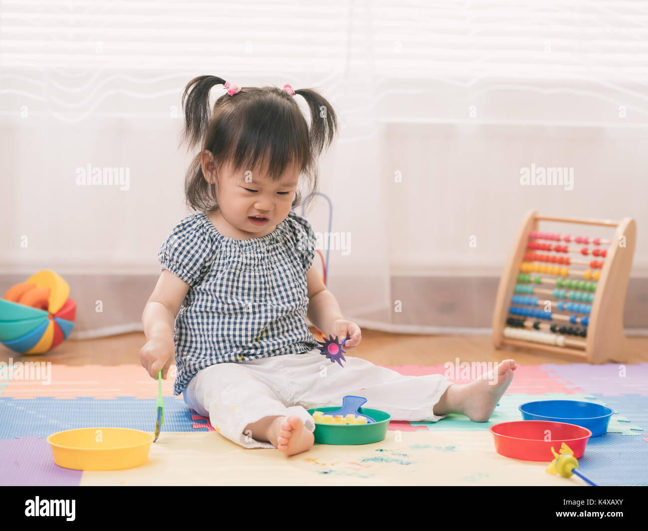 Bambina gioca dito dipinge a casa Immagini Stock