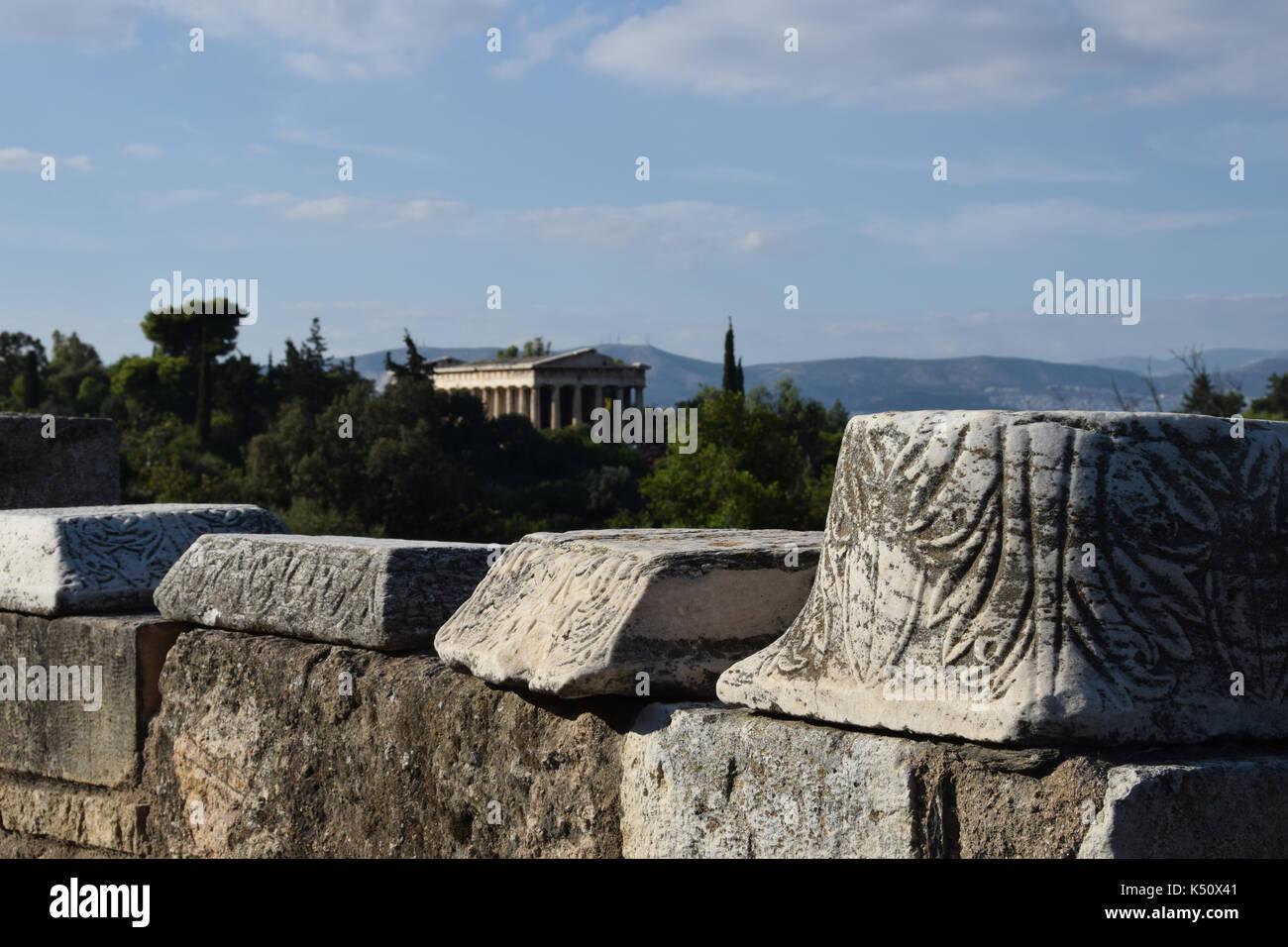 Parete con la colonna di marmo frammenti con ornamenti intagliati all'antica agorà di Atene in Grecia. il tempio di Efesto può essere visto in background Foto Stock