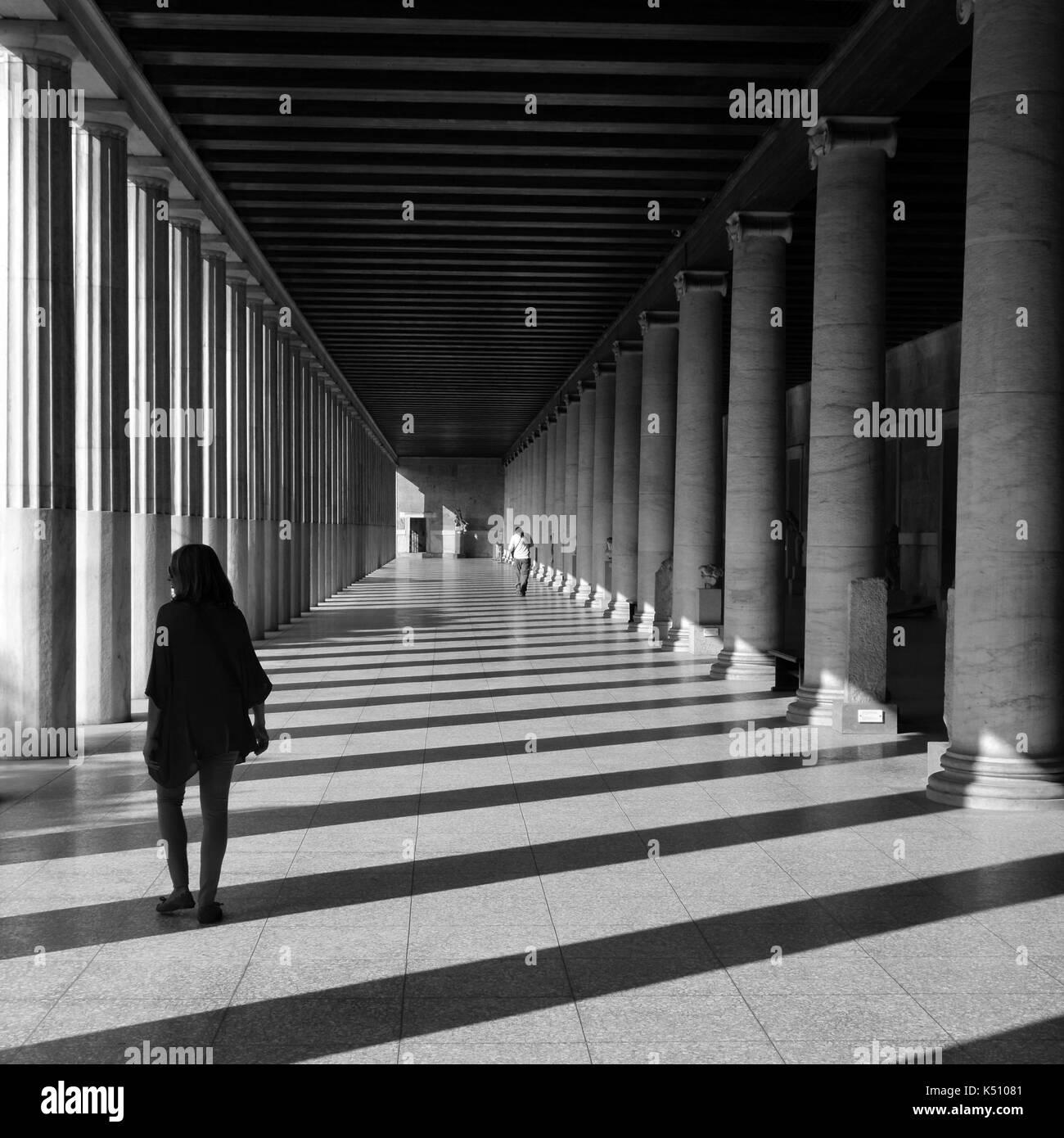 Athens, Grecia - 14 ottobre 2015: la gente in Stoa di Attalos l antica agora. luce e ombra attraverso colonne di marmo architettura astratta di un nero Foto Stock