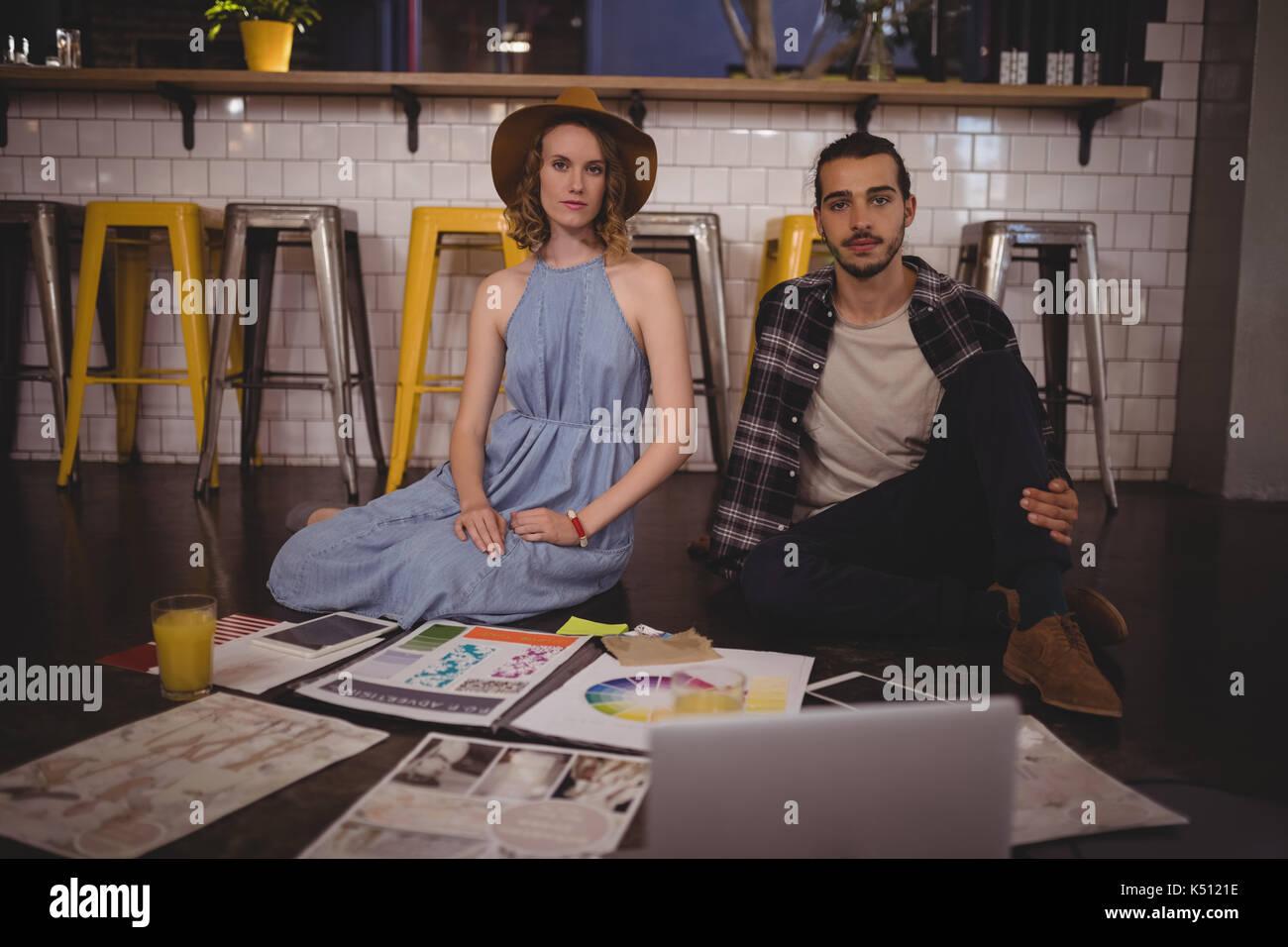 Ritratto di giovani creativi professionisti seduti sul pavimento con le carte presso la caffetteria Immagini Stock