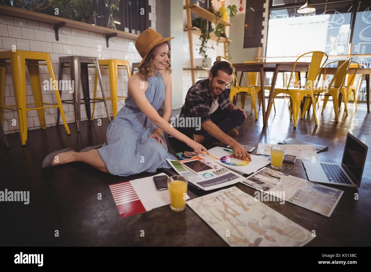 Sorridente giovani professionisti con i fogli e le tecnologie seduto sul pavimento nel coffee shop Immagini Stock