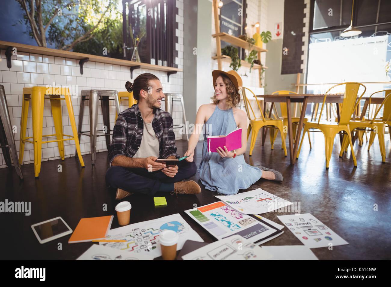 Allegro giovani professionisti seduti con fogli sul pavimento nel coffee shop Foto Stock