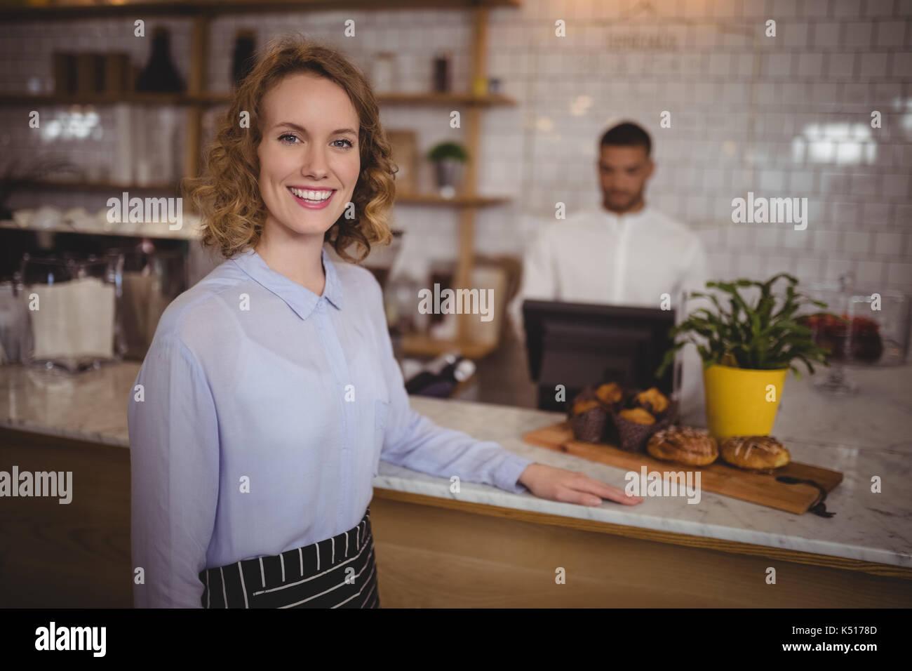 Ritratto di cameriera fiducioso in piedi dal contatore al coffee shop Immagini Stock