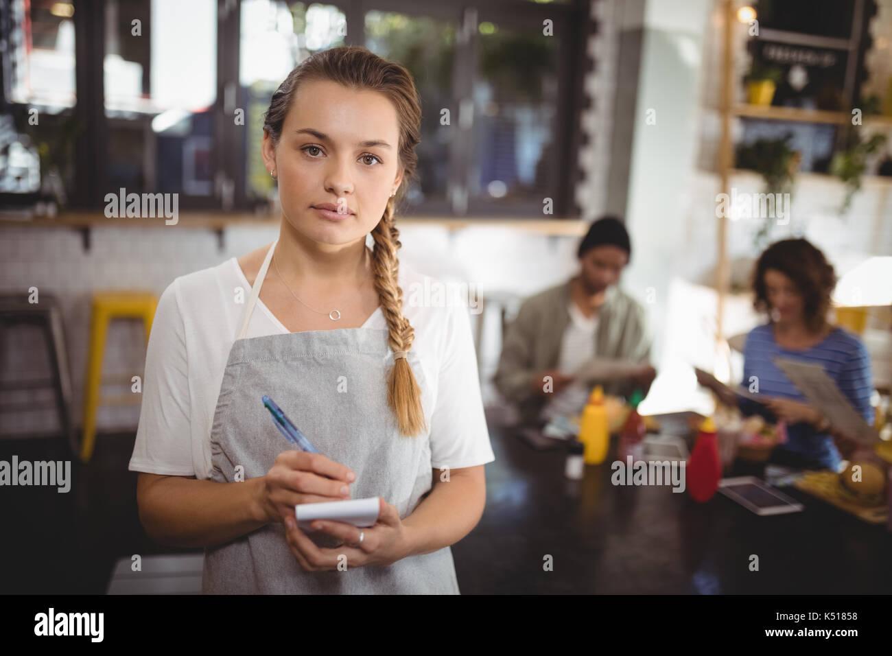 Ritratto di fiducioso giovane cameriera in piedi con il blocco note al cafe Immagini Stock