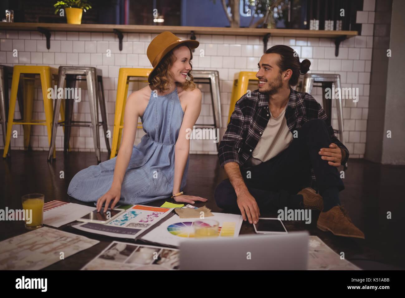 Sorridente giovani designer seduto con i fogli sul pavimento nel coffee shop Immagini Stock