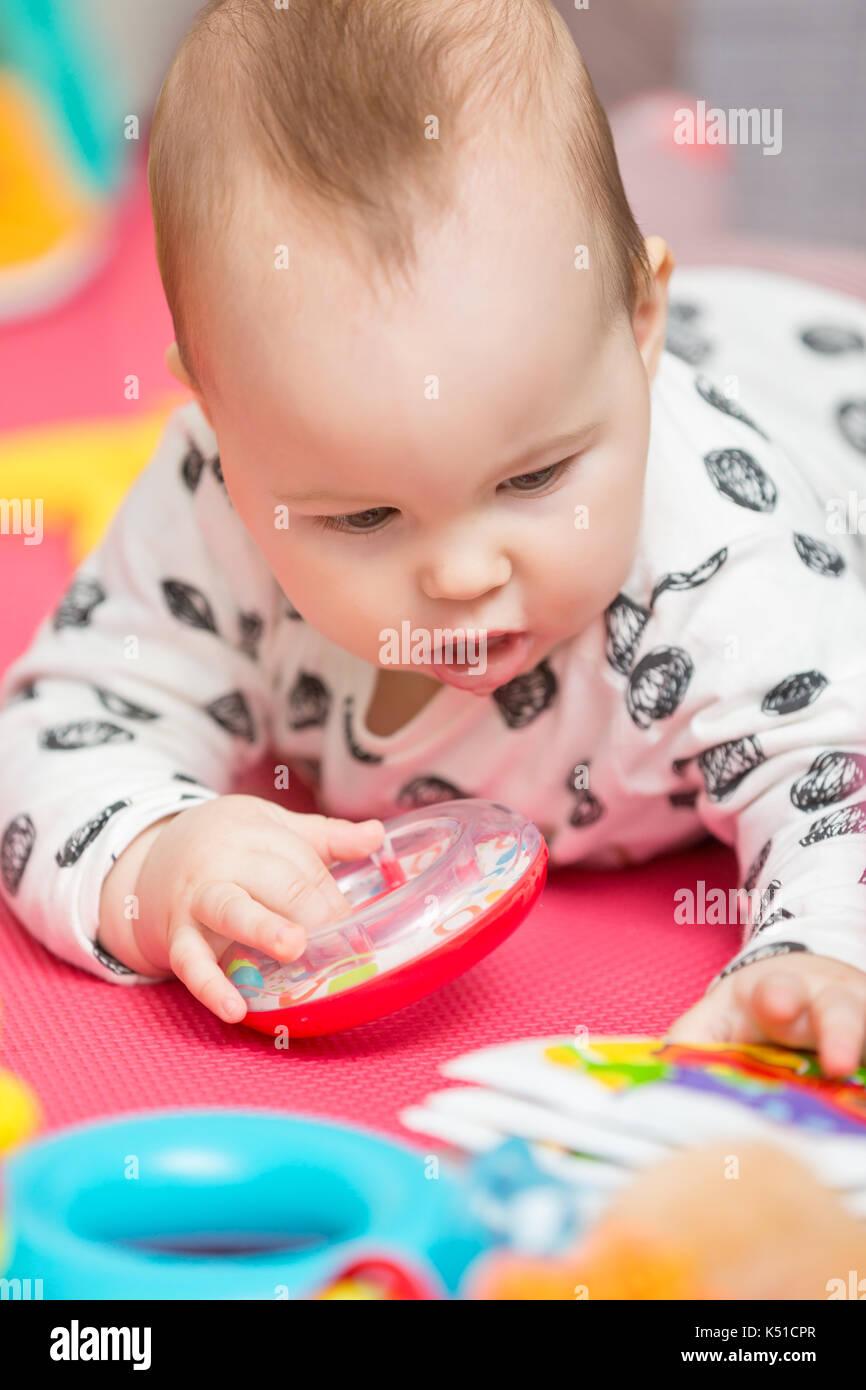 4ae154a06f Sette mesi Baby girl giocare con giocattoli colorati su un tappetino ...