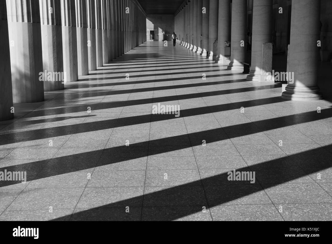 Athens, Grecia - 14 ottobre 2015: uomo a camminare tra le colonne del gruppo di lavoro Stoa di Attalos l antica agora. luce e ombra architettura astratta di un nero Foto Stock