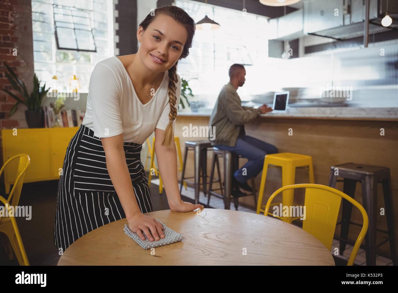 Ritratto di giovane cameriera tabella di pulizia presso il cafe Immagini Stock