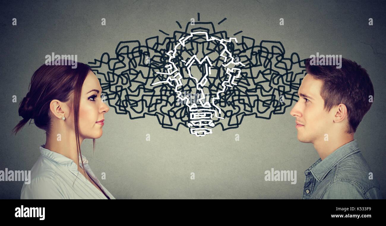 Giovane uomo e donna che guarda ad ogni altra scambiando i loro pensieri in arrivo insieme con un'idea lampadina Immagini Stock