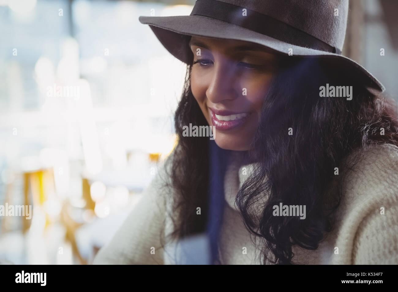 Close-up di giovane donna che indossa il cappello in cafe Immagini Stock