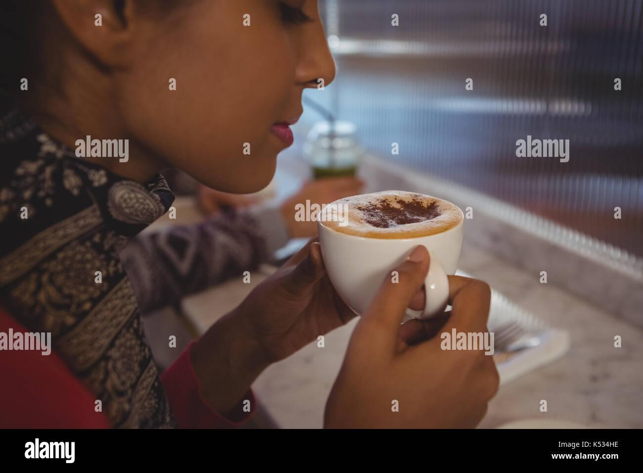 Close-up di giovane donna avente caffè nella caffetteria Foto Stock
