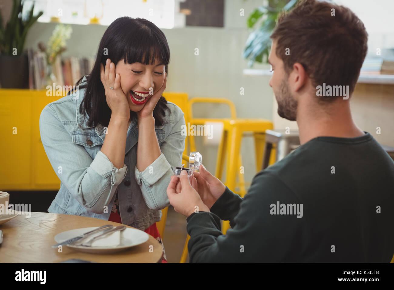 Giovane uomo gifting anello per scioccato donna felice in cafe Immagini Stock