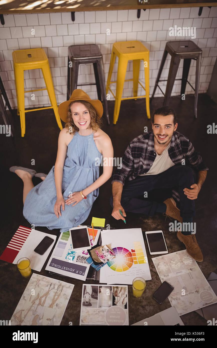 Angolo alto ritratto di sorridere i giovani creativi professionisti seduti sul pavimento con fogli presso la caffetteria Immagini Stock