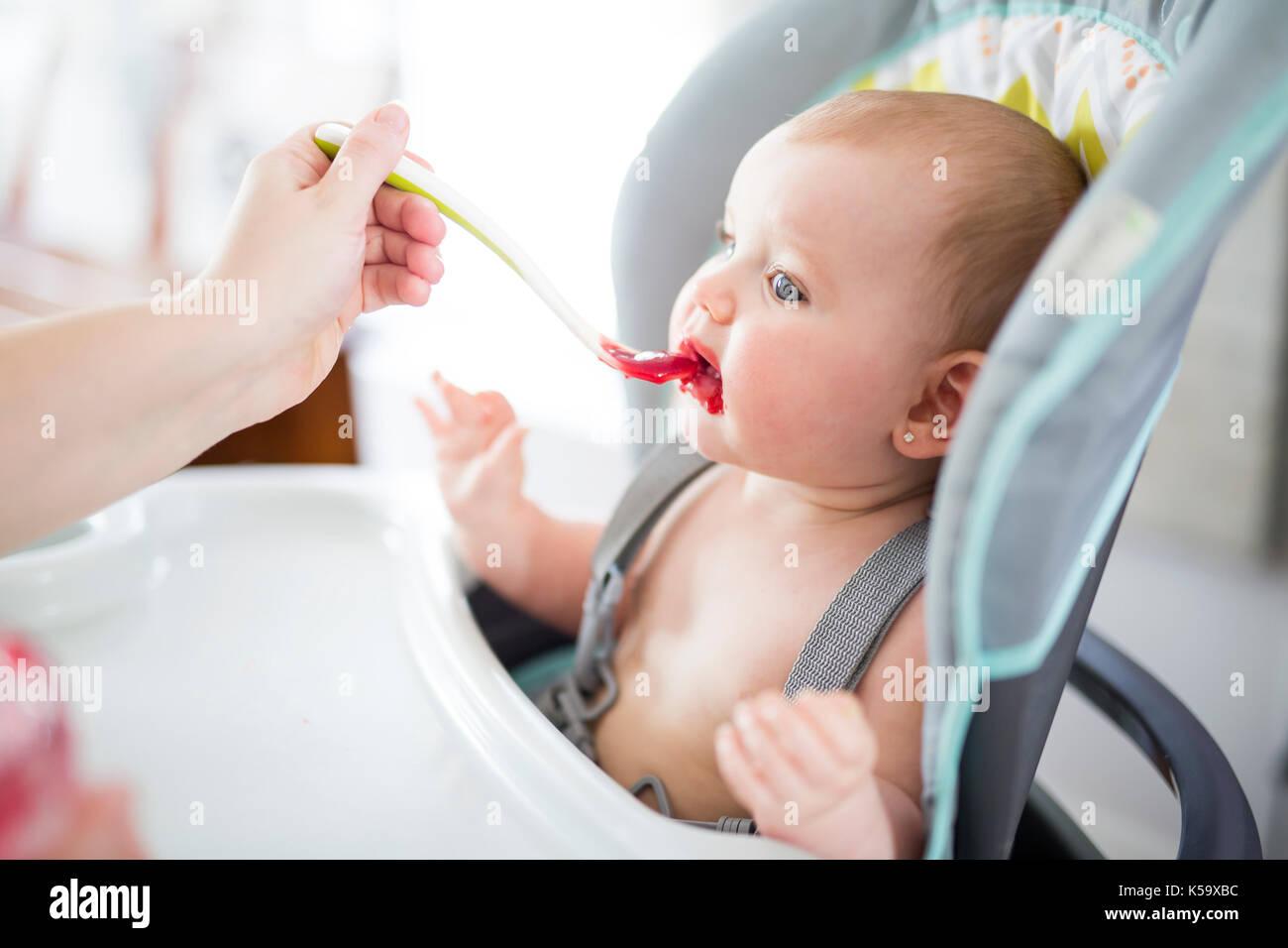 Alimentazione madre bambina in sedia alta Immagini Stock