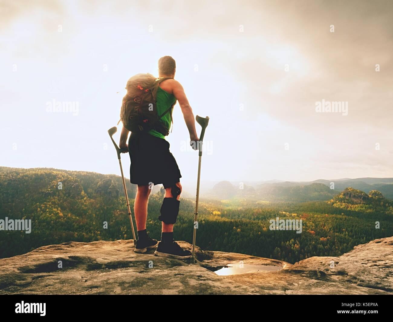 Uomo con le stampelle e la gamba rotta fissata in ortesi per ginocchio caratteristica.traveler con gamba ferito in bendaggi soggiorno sul roccioso punto di vista nelle montagne. escursionista con Immagini Stock