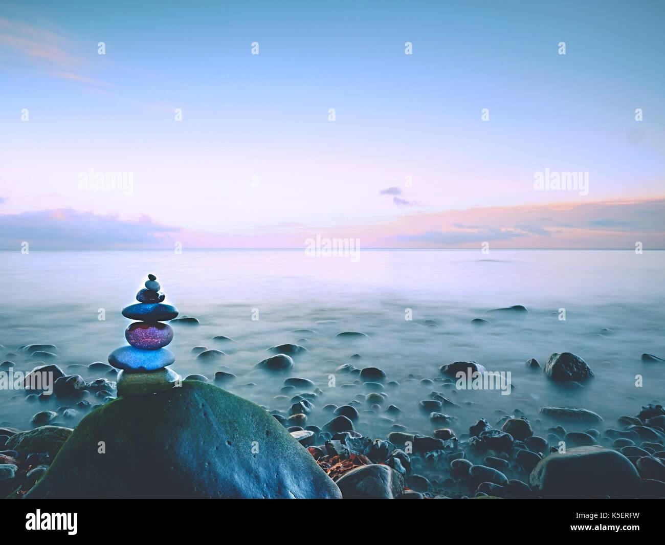 Arrotondate le pietre colorate stand in forma di piramide grande pietra arrotondata in acqua di mare Immagini Stock