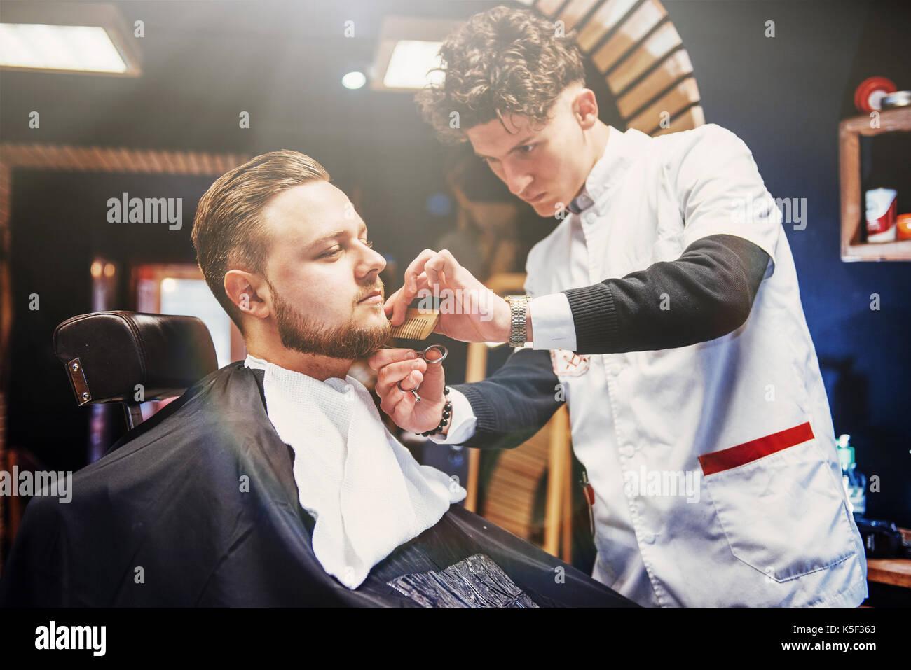 Uomini acconciature e taglio di capelli in un negozio di barbiere o  parrucchiere. Immagini Stock 10355100f0f9