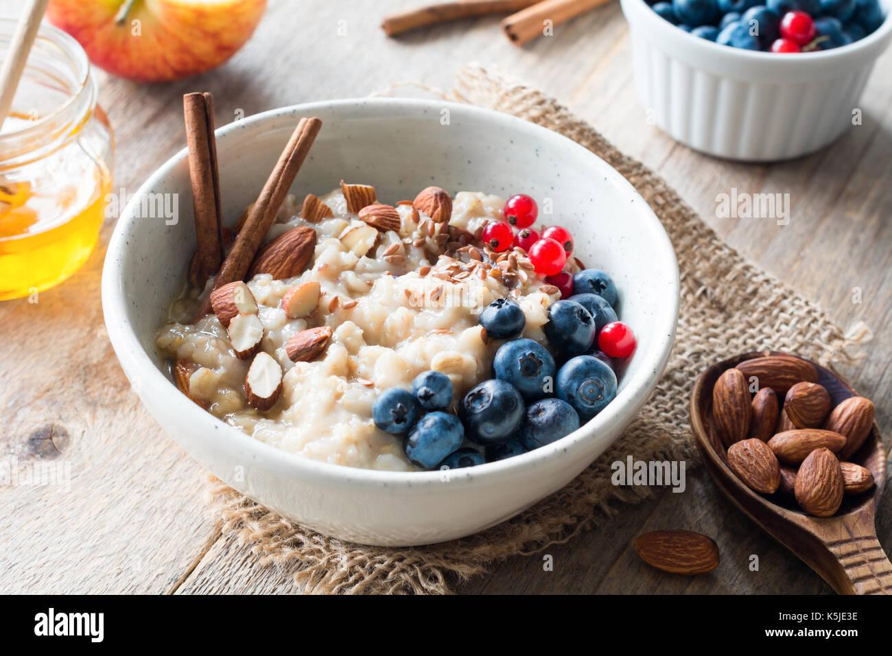 Farina di avena porridge con mirtilli, le mandorle e la cannella, il miele, i semi di lino e di ribes rosso nel recipiente. Super alimenti per una sana colazione nutriente Immagini Stock