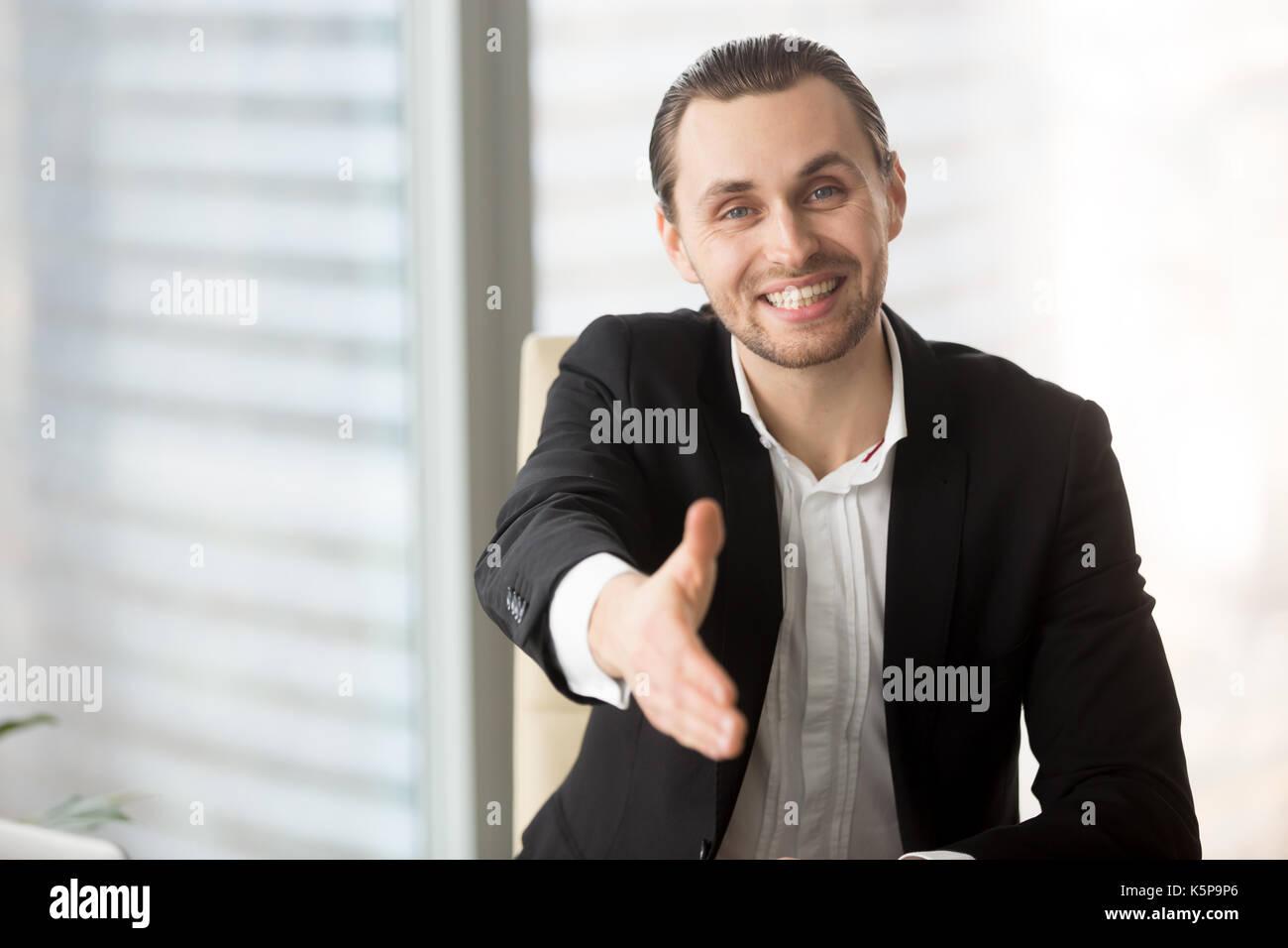 Gentile imprenditore sorridente offrendo la mano per il messaggio di saluto o d'accordo Immagini Stock
