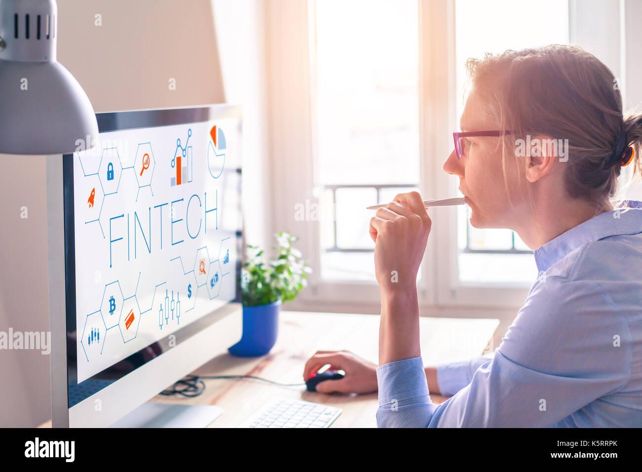 Concetto di fintech sullo schermo del computer con interfaccia moderna e innovativa di grafici, femmina persona business in ufficio Immagini Stock