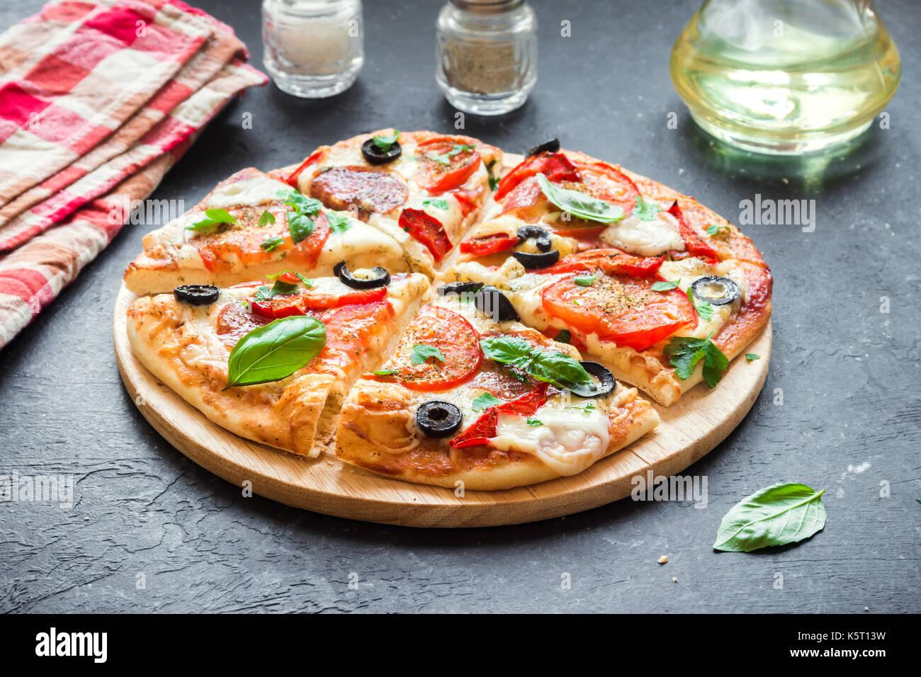 Italian pizza con pomodori, salame, olive nere e mozzarella, vista dall'alto. freschi fatti in casa la pizza. Immagini Stock