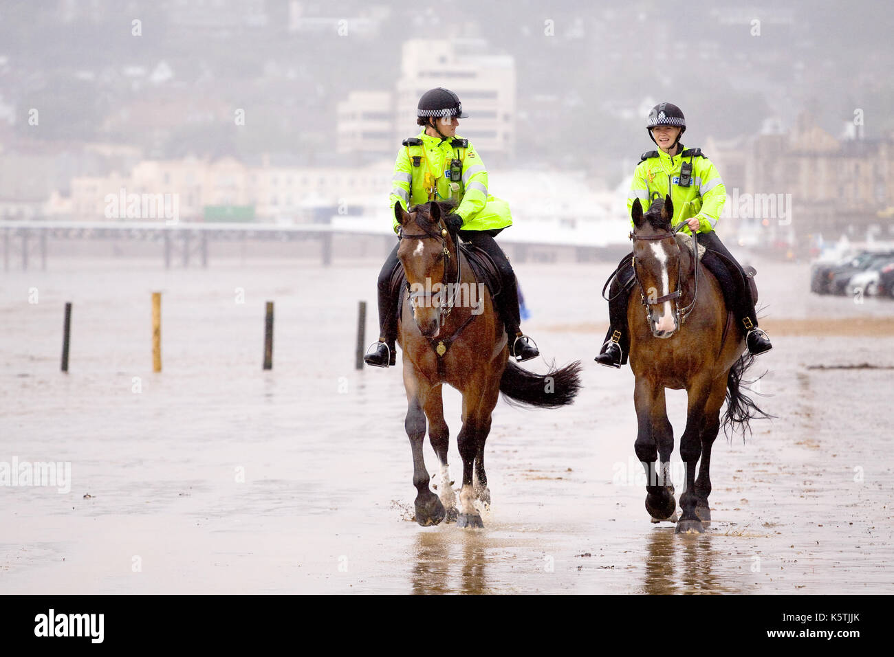Due mouned donna di polizia, di pattuglia, in divise fluorescenti a cavallo.la loro polizia cavalli lungo una spiaggia in wet ventoso. Immagini Stock