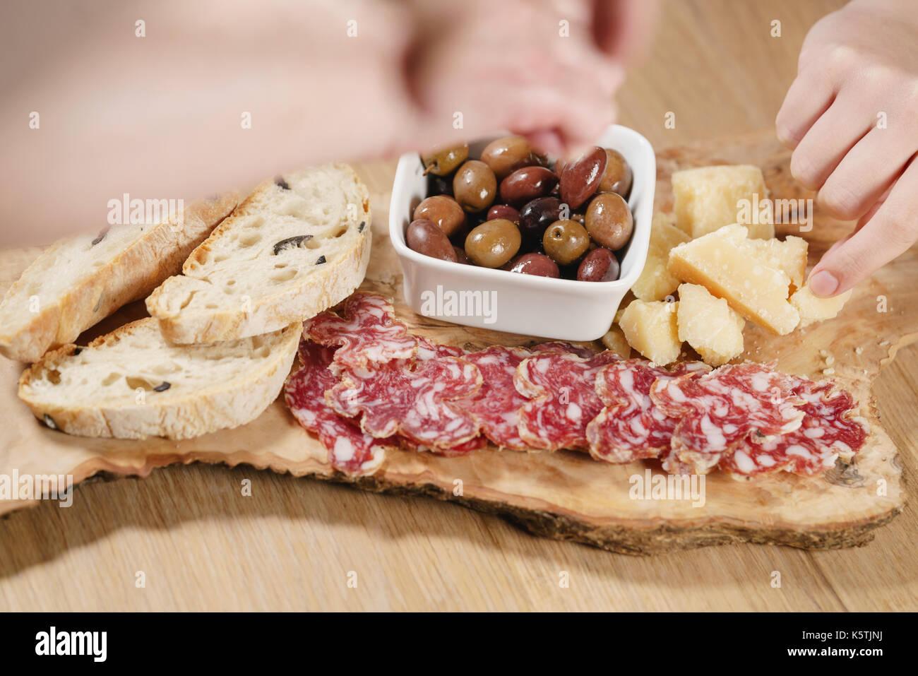 Le mani prendendo antipasti italiani stuzzichini sul tavolo closeup Immagini Stock