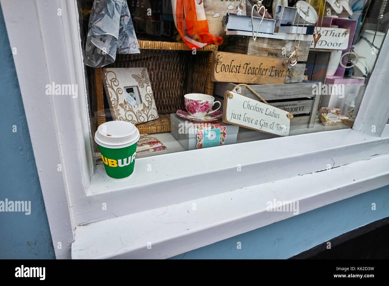 Cheshire cari solo amore un gin tonic accedi alla vetrina di un negozio con una metropolitana tazza di caffè al di fuori Immagini Stock
