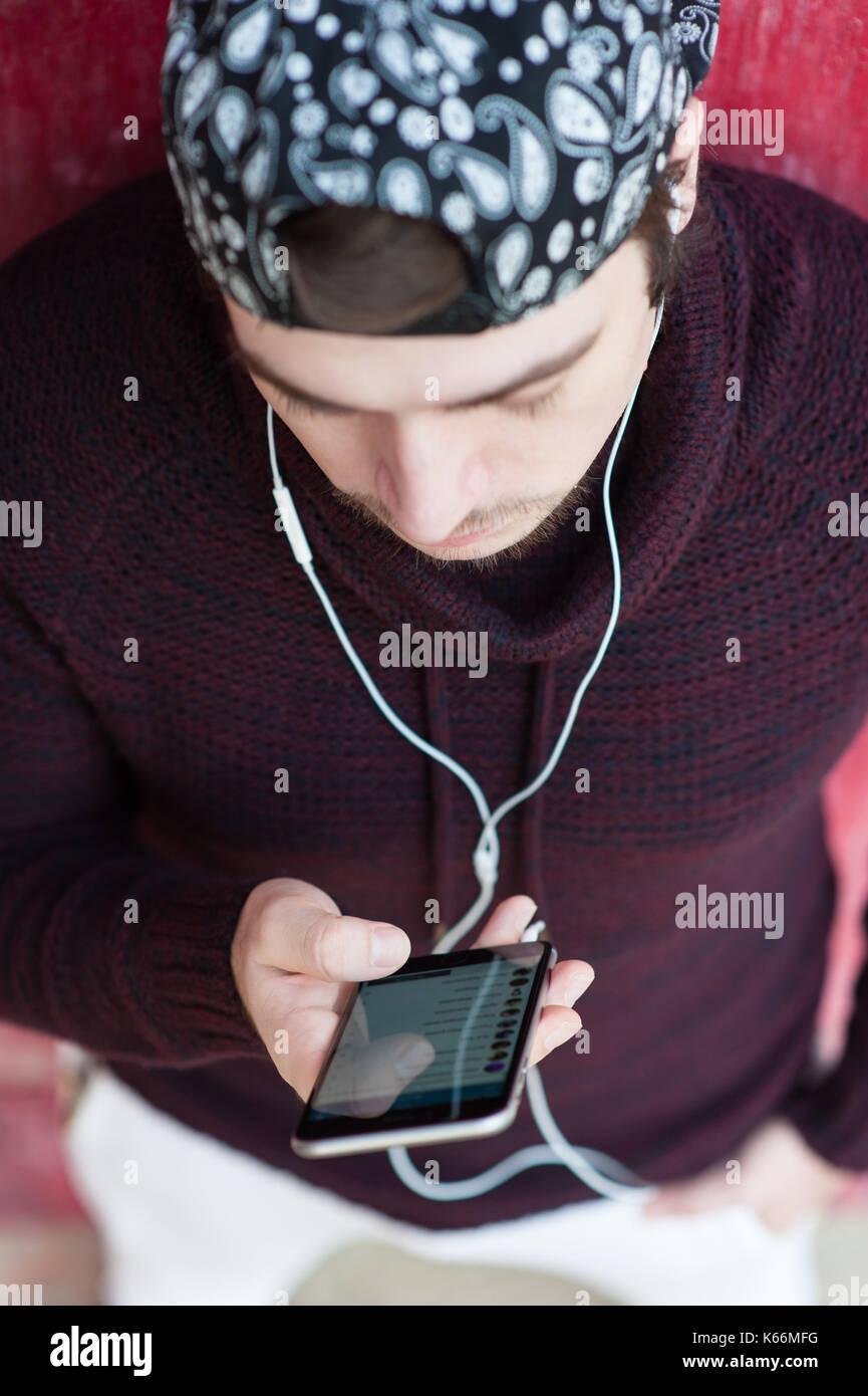 Bel giovane uomo che indossa un maglione di lana e cappello da baseball con  lo smartphone 166dc220b834