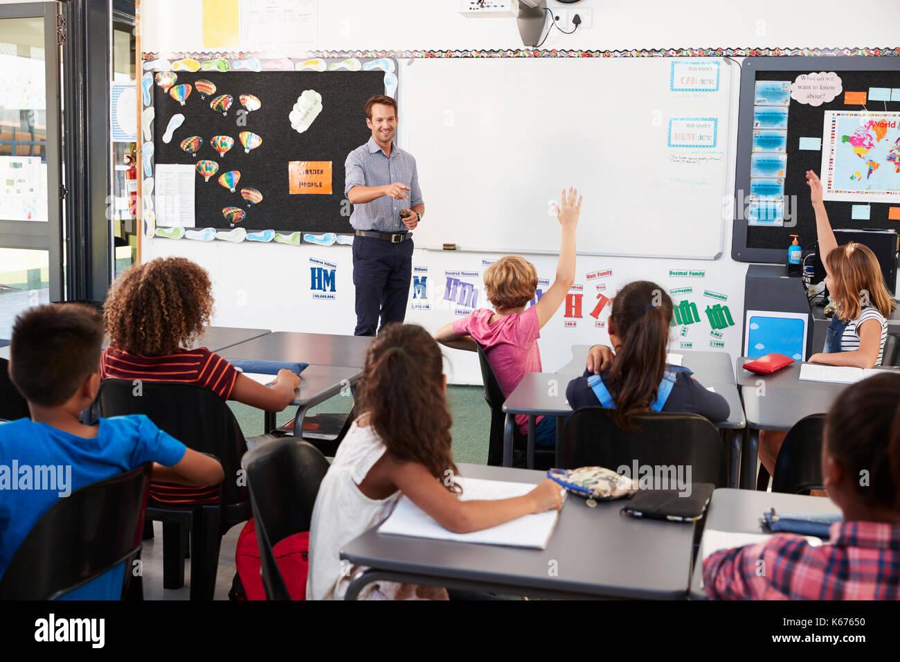 Docente alla parte anteriore della classe in una scuola elementare lezione Immagini Stock