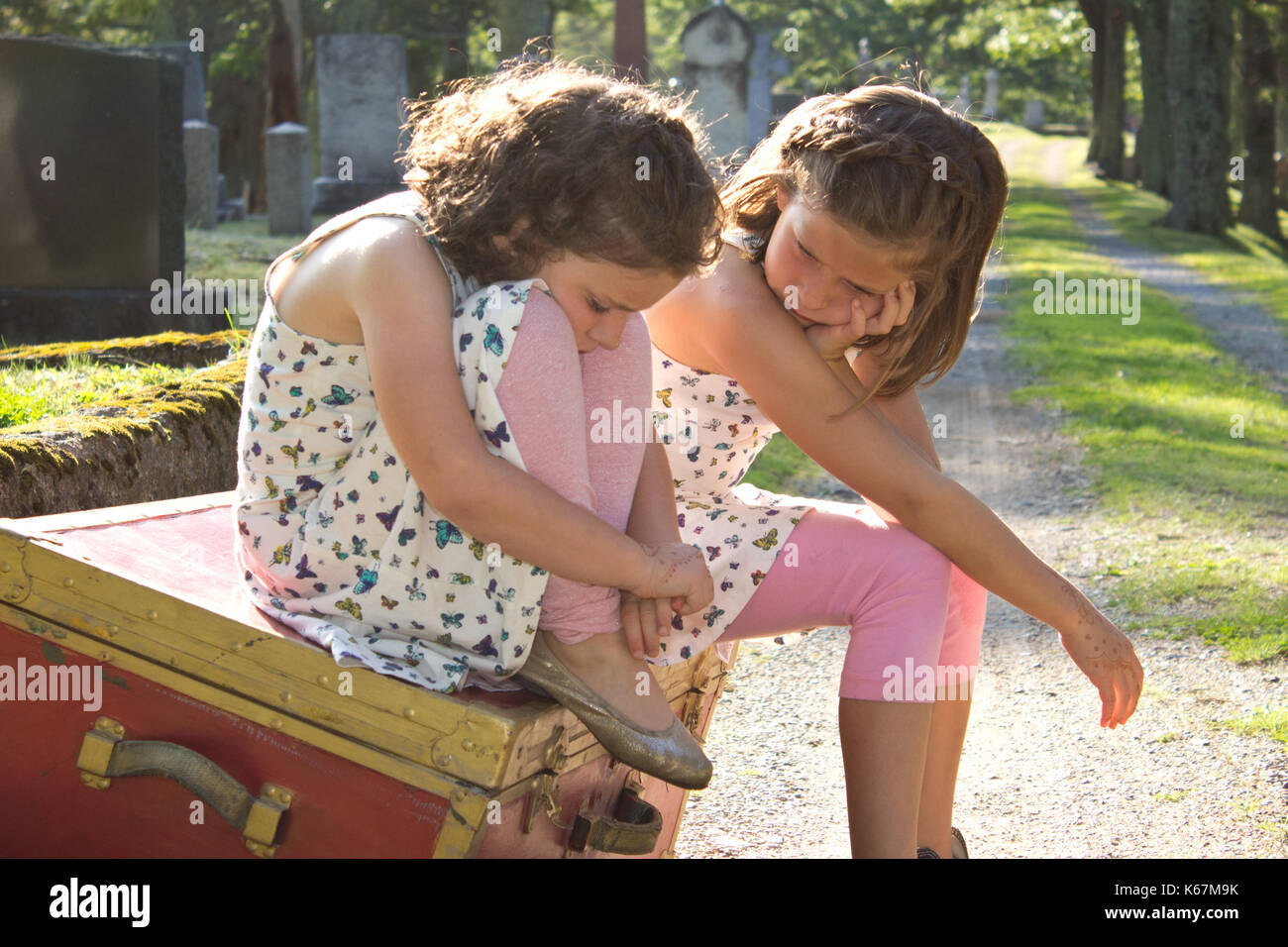 Due triste dai capelli marroni le ragazze a sedersi su una casella rossa nel cimitero con espressioni triste Immagini Stock